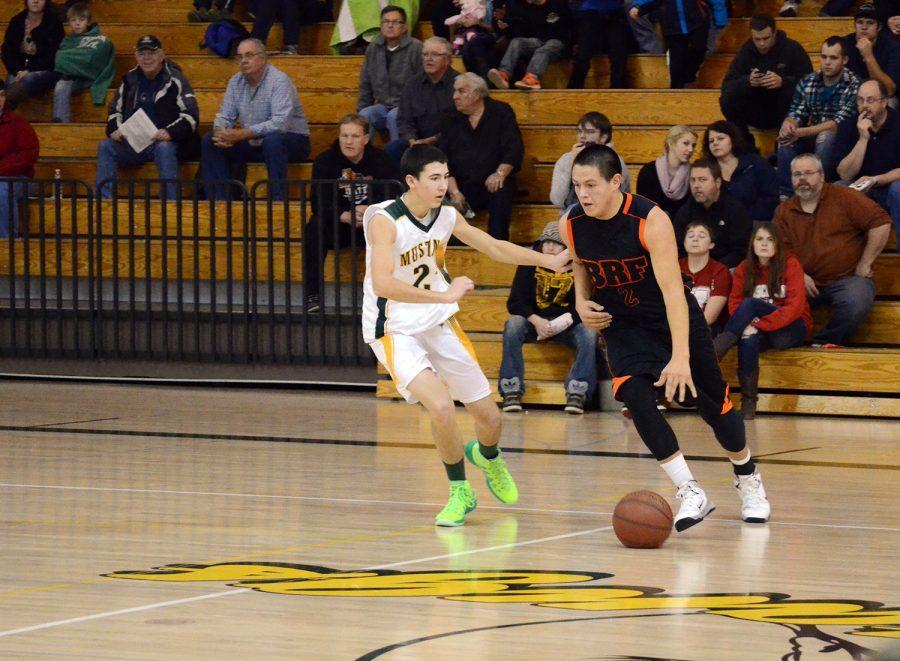 Senior starter Junior Gulbronson pushes the ball down court. Gulbronson scored 20 points in the game against the Mustangs.