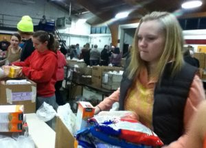 FUN WITH PACKING NHS member Sam Barnum helps pack boxes for families in need at Project Christmas.  NHS members were given the opportunity to volunteer at Project Christmas to complete their 10 hours.