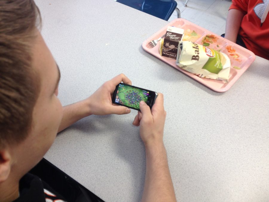 Kyle+Peterson+plays+Clash+of+Clans+during+lunch.+He+is+one+of+many+students+that+takes+advantage+of+this+allowed+time+to+play+on+phones+during+lunch.